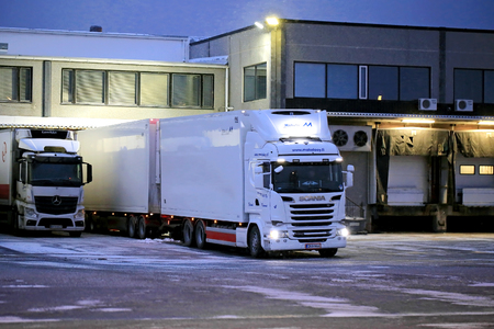 SALO, Finland - 27 november 2016: Grote witte koelwagen vrachtwagen klaar om te lossen op warehause in de winter 's avonds sneeuwval.