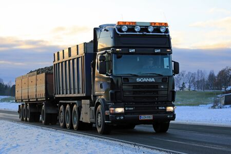 grille: SALO, FINLAND - NOVEMBER 11, 2016: Black Scania 164L 580 trailer truck transports sugar beet from the fields to the sugar factory on an early winter evening in South of Finland. Editorial