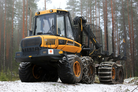 gripper: SALO, FINLAND - DECEMBER 18, 2016: PONSSE Elk forest forwarder in foggy pine forest in winter. The Elk has the load carrying capacity of 13 000 kg.