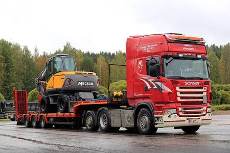 cargador frontal: Padasjoki, FINLANDIA - 4 de septiembre, 2016: Red Scania R560 de Kuljetus J. Kontinen Ky transporta Mecalac 714MWe excavadora de ruedas en el remolque cubierta gota. Editorial