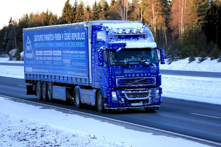 very cold: SALO, FINLAND - JANUARY 5, 2017: Blue Volvo FH12 460 of Saps Trans with frost and snow on the vehicle transports goods along freeway in very cold weather conditions in South of Finland.