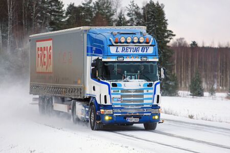 big slick: SALO, FINLAND - JANUARY 7, 2017: Customized Scania 164L 480 semi truck and curtainsider trailer of L. Retva Oy snowy winter road in South of Finland. Editorial
