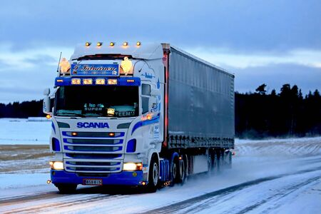 super highway: SALO, FINLAND - JANUARY 7, 2017: Customized Super Scania of T. Salminen Transport semi trailer moves along snowy highway at dusktime in South of Finland. Editorial