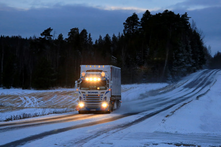 SALO, FINLAND - JANUARY 7, 2017: Customized Super Scania semi truck of T. Salminen Transport with shiny headlights hauls goods at dusktime along snowy and icy winter road.