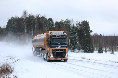 delivers: SALO, FINLAND - JANUARY 7, 2017: Volvo FH semi tank truck of J. Mettala Ky for bulk transport delivers a load along a snowy highway in winter. Editorial