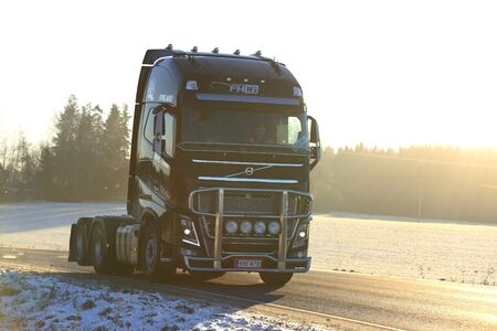 highway 6: SALO, FINLAND - JANUARY 6, 2017: Black Volvo FH semi tractor of MHL Trans moves along winter highway in the golden light of sunset. Editorial