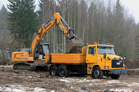tracked: FORSSA, FINLAND - JANUARY 28, 2017: Liebherr R 918 crawler excavator loads soil onto yellow Sisu SR 332 tipping truck in winter. Editorial
