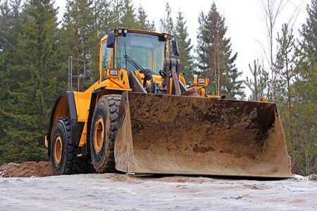 cargador frontal: Cargador de ruedas amarillo en el sitio de construcción de carreteras rurales en invierno.