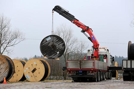 Salo, Finlandia - 17 lutego 2017: Żuraw montowany na ciężarówce rozładowuje bębny kabli zasilających na podziemnym placu budowy. W okolicy kable napowietrzne zostaną zastąpione kablami podziemnymi. Publikacyjne