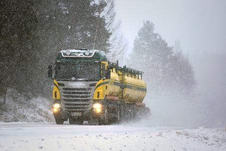 SALO, FINLAND - FEBRUARY 24, 2017: Colorful tank truck of Kuljetusliike K. Pekki transports goods along snowy, slippery road during a blizzard.