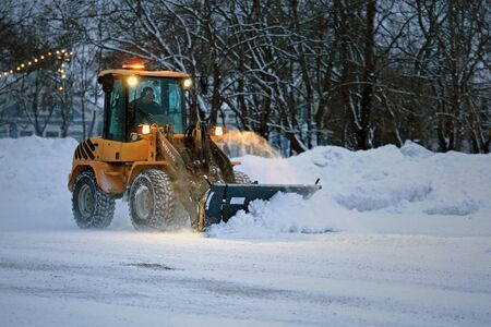 SALO, FINLAND - FEBRUARY 24, 2017: Snow removal with Volvo L35B compact wheel loader equipped with snowplow on a winter evening in South of Finland.