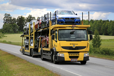 hauler: KARJAA, FINLAND - JUNE 11, 2016: Yellow Renault Premium car carrier of SE Makinen transports new cars along highway on a beautiful day of summer.