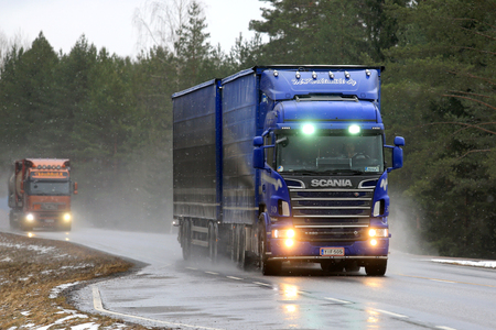light duty: SALO, FINLAND - MARCH 4, 2017: Blue Scania R620 combination vehicle of M. Keskimaki and another truck transport goods along wet road in snowfall. Editorial