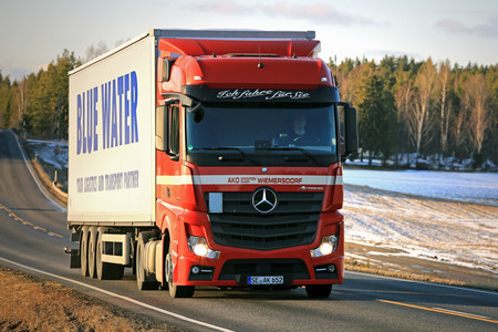SALO, FINLAND - MARCH 4, 2017: Red Mercedes-Benz Actros 1845 semi truck of AKO Spedition hauls Blue Water trailer at dusktime in South of Finland. Blue Water Shipping is an international shipping, transport and freight forwarding company.