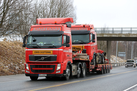 RAASEPORI, FINLAND - MARCH 11, 2017: Red Volvo FH 460 transports an identical Volvo truck on lowboy trailer as exceptional load along highway in South of Finland at spring. Editorial