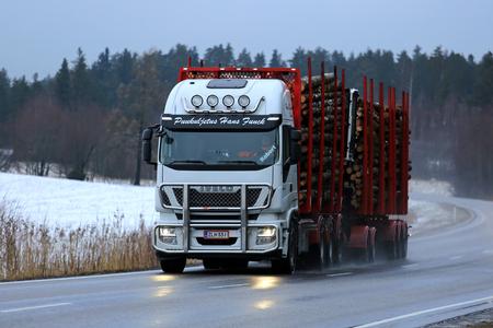 SALO, FINLANDIA - 10 de marzo de 2017: camión de registro blanco Iveco Stralis 560 de Puukuljetus Hans Funck transporta una carga de troncos a lo largo de la carretera mojada en la hora azul de una tarde de invierno en el sur de Finlandia.