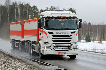 SALO, FINLAND - MARCH 10, 2017: White customized Scania R730 combination vehicle of Transport Stromberg trucking along rural highway on a rainy day in March.