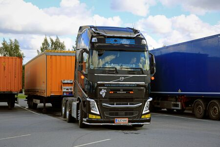 truck driver: ALAHARMA, FINLAND - AUGUST 12, 2016: Black Volvo FH truck driver detaches a cargo trailer at a truck stop yard. Editorial