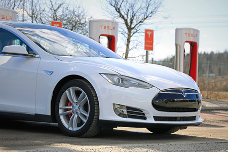 PAIMIO, FINLAND - MARCH 18, 2017: Detail of white Tesla Model S P85D electric car which is being charged at Tesla Supercharger. The Supercharger stations will add ca 150 miles in about 20 minutes.