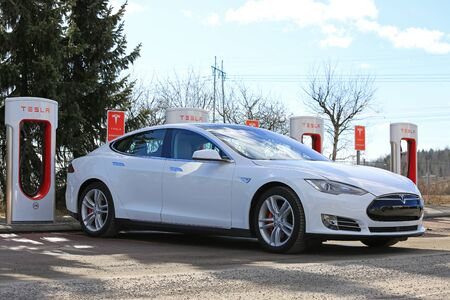 PAIMIO, FINLAND - MARCH 18, 2017: White Tesla Model S P85D electric car is being charged at Tesla Supercharger. The Supercharger stations will add ca 150 miles in about 20 minutes. Sajtókép