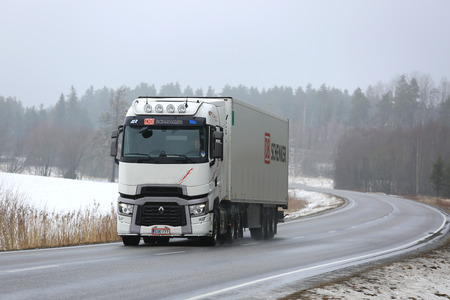 SALO, FINLAND - MARCH 10, 2017: White Renault Trucks T semi trailer transports cargo along road on a foggy day in winter.