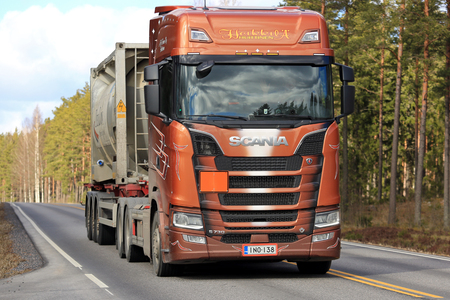 hauler: SALO, FINLAND - MARCH 24, 2017: Next Generation Scania S730 semi of Heikkila for ADR transport moves ahead on rural highway at spring.