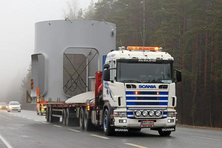 FORSSA, FINLANDIA - 2 DE ABRIL DE 2017: Scania semi-gran tamaño de transporte de un objeto industrial por KVL Kuljetus se mueve a lo largo de la carretera en un día de niebla. Detrás del vehículo, un coche de escolta advierte tráfico.