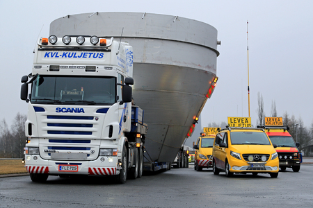 FORSSA, FINLAND - APRIL 2, 2017: Wide load transports of max 7,6 m wide industrial objects by two Scania trucks and four escort cars take a break at a truck stop.