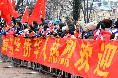 HELSINKI, FINLAND - APRIL 5, 2017: Chinese fans wave Finnish and Chinese flags as they wait to see President Xi Jinping who is visiting Finland in April 5-6, 2017.
