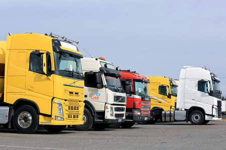 FORSSA, FINLAND - APRIL 9, 2017: Line up of colorful new and used Volvo and Scania semi trucks on asphalt yard on a cloudy day.
