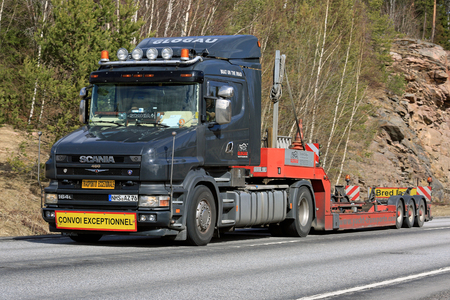 KARJAA, FINLAND - APRIL 8, 2017: Black conventional Scania 164L 480 empty gooseneck trailer of Glogau Yachttransporte for boat transport moves along highway in South of Finland at spring.