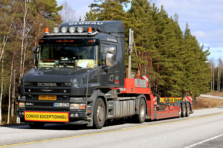 RASEBORG, FINLAND - APRIL 8, 2017: Black conventional Scania 164L 480 empty gooseneck trailer of Glogau Yachttransporte for boat transport moves along highway in South of Finland at spring.