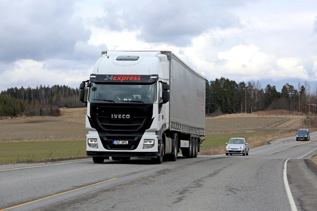 hiway: SALO, FINLAND - APRIL 13, 2017: White Iveco Stralis Hi-Way semi truck hauls curtainsider trailer among traffic on a cloudy day of spring.