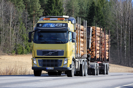 SALO, FINLAND - APRIL 21, 2017: Yellow Volvo FH16 logging truck transports a load of pine logs along highway at spring.