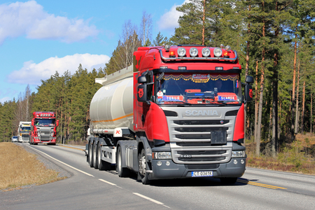 SALO, FINLAND - APRIL 21, 2017: Customized red Scania R440 semi tanker leads a convoy of three Polish semi tank trucks along highway on a sunny day in Finland.