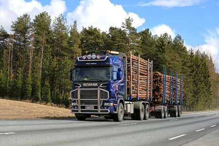 JOKIOINEN, FINLAND - APRIL 23, 2017: Blue Scania logging truck of Aaltonen transports pine timber along highway on a beautiful day of spring.