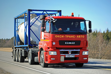 FORSSA, FINLAND - MAY 1, 2017: Red Russian Kamaz T1840 truck transports tank container along road in Finland, where the Kamaz are seldom seen. The truck driver shows thumbs up gesture. Editorial