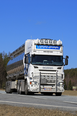 JOKIOINEN, FINLAND - MAY 1, 2017: Customized white Scania semi tank truck with bull bar and lighting accessories for Haanpaa on the road on a sunny day of spring. Editorial