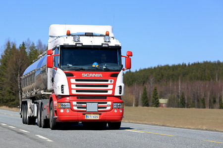 JOKIOINEN, FINLAND - MAY 1, 2017: Red and white Scania R500 semi tank truck for bulk or liquid transport moves along road on a beautiful sunny day.