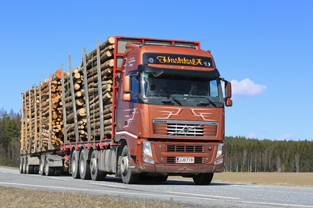JOKIOINEN, FINLAND - MAY 1, 2017: Brown Volvo FH truck of Kuljetusliike Ano Heikkila Oy hauls a full timber load along highway on a sunny day of spring.