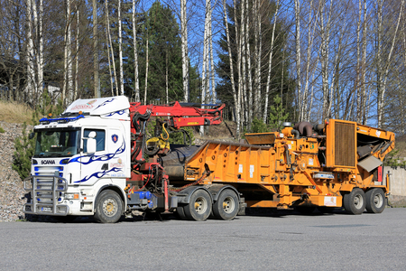 hauler: SALO, FINLAND - MAY 5, 2017: Scania truck mounted equipment for recycling forestry residues parked on a yard. Logging refuse can be further used as source of energy. Editorial