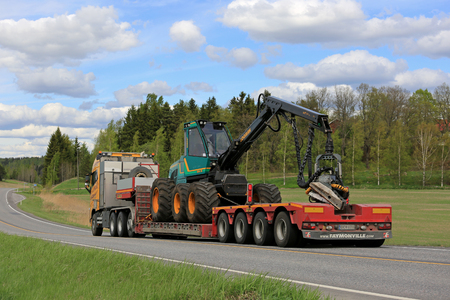 SALO, FINLAND - MAY 25, 2017: Yellow Volvo FH of Kosken Autokeskus transports Logman 811H forest harvester on gooseneck trailer along highway on a beautiful day of spring. Editorial