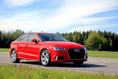 KAARINA, FINLAND - JUNE 3, 2017: New beautiful Tango red Audi A3 Sedan Business Sport 2017 parked on side of highway on a clear day of early summer.
