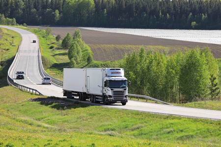 HALIKKO, FINLAND - JUNE 4, 2017: White Scania R450 refrigerated transport truck of Ralf Hellsberg Oy on the road through agricultural landscape in South of Finland at summer.