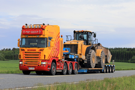JOKIOINEN, FINLAND - JUNE 16, 2017: Customized Scania G580 truck gooseneck trailer of PHP Group transports large wheel loader along highway at summer. Editorial