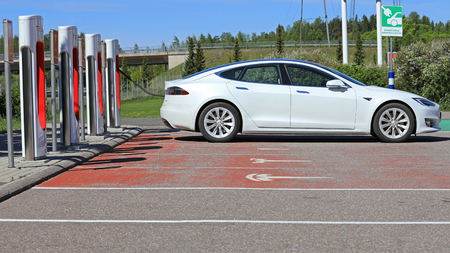 PAIMIO, FINLAND - JUNE 3, 2017: White Tesla Model S electric car charges battery on Tesla Supercharger Station in Paimio, Finland on a sunny day. Editorial
