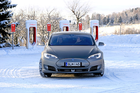 PAIMIO, FINLAND - JANUARY 17, 2016: Tesla driver waves as the vehicle leaves Tesla Supercharger Station after charging battery of their Tesla Model S electric car on a cold wintery day. Unlike conventional cars, electric cars will always start in winter.