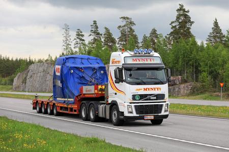 PAIMIO, FINLANDIA - 9 DE JUNIO DE 2017: El camión blanco de Volvo FH16 de Myntt Oy transporta el objeto industrial de ABB en el remolque como carga ancha en el sur de Finlandia.