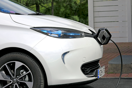 ze: FORSSA, FINLAND - JUNE 23, 2017: Renault Zoe ZE 40 electric car is plugged in to charge battery. The Zoe supports AC charging only.