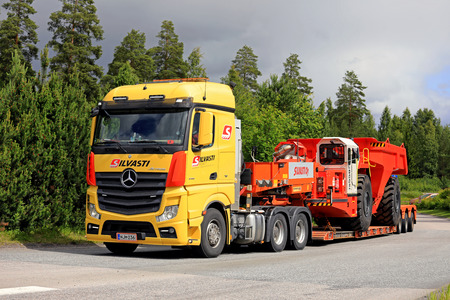daimler: LEMPAALA, FINLAND - JULY 6, 2017: Mercedes-Benz Actros 3351 of Silvasti Heavy transports Sandvik Underground Truck on gooseneck trailer along road. The mining vehicle is being transported from Finland to Bulgaria. Editorial